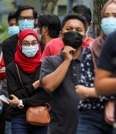 FILE PHOTO: People wait in line to be tested for the coronavirus disease (COVID-19) in Shah Alam, Malaysia January 7, 2021. REUTERS/Lim Huey Teng/File Photo